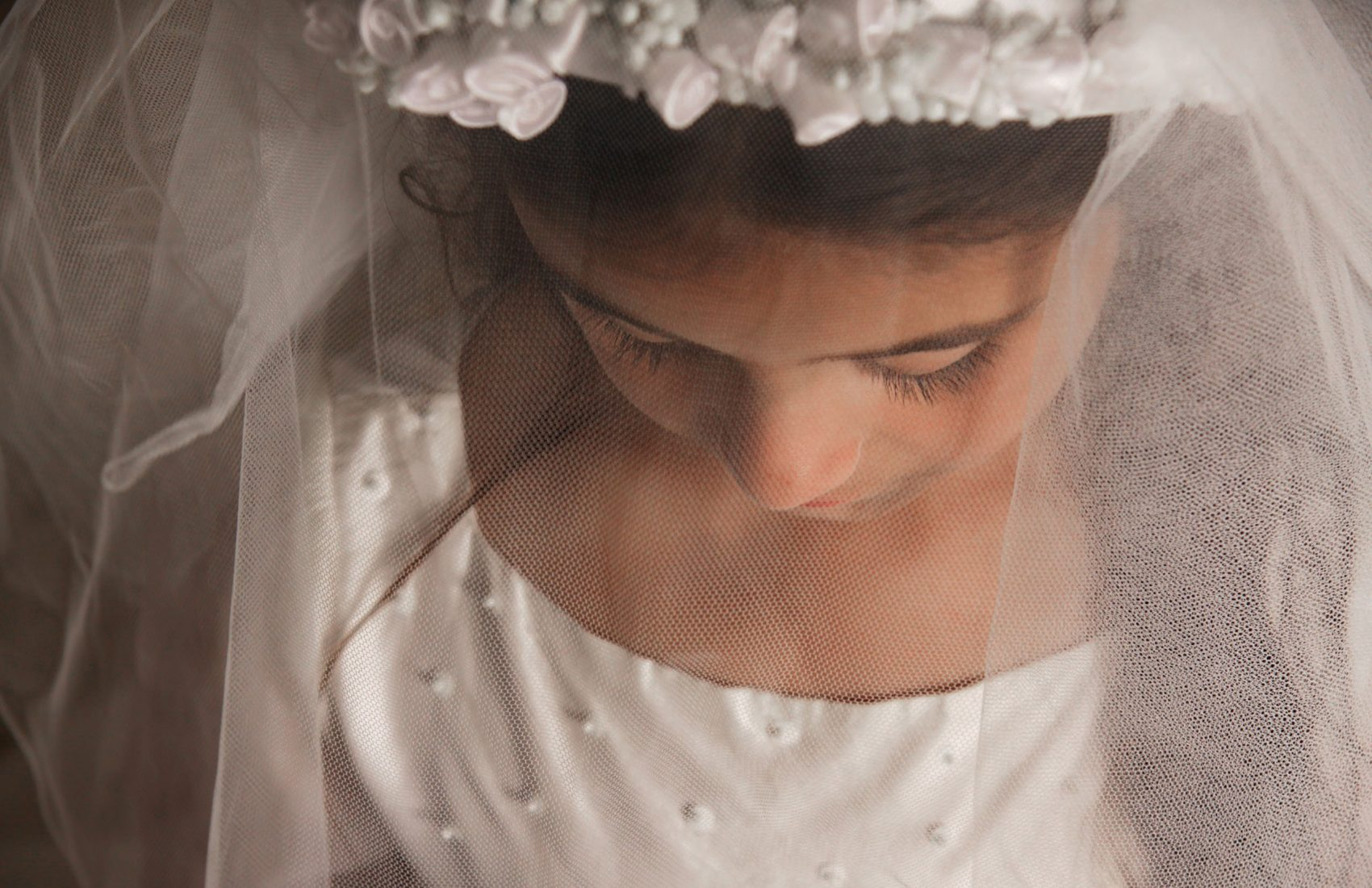 A young girl preparing for her holy communion, photographed with her veil covering her face and looking down
